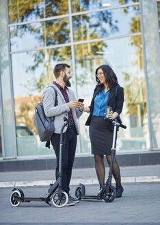 Happy businessman and businesswoman with scooters talking on pavement - ZEDF01701