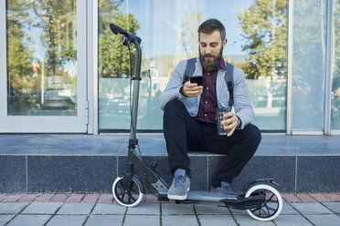 Businessman sitting outdoors using cell phone next to scooter - ZEDF01704