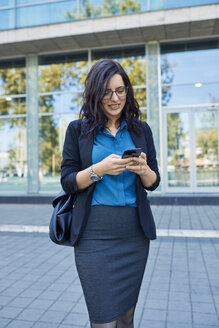 Smiling businesswoman using cell phone in front of office building - ZEDF01707