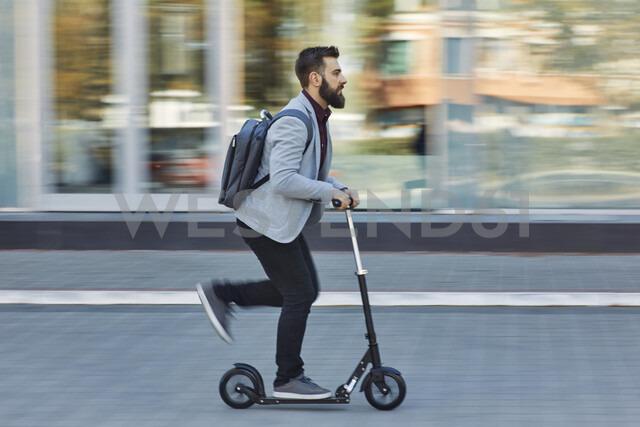 Businessman riding scooter along office building - ZEDF01713 - Zeljko Dangubic/Westend61