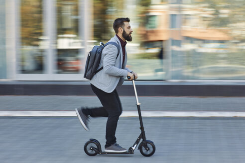 Businessman riding scooter along office building - ZEDF01713