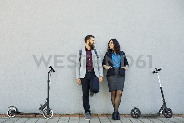 Smiling businessman and businesswoman with scooters leaning against a wall - ZEDF01722