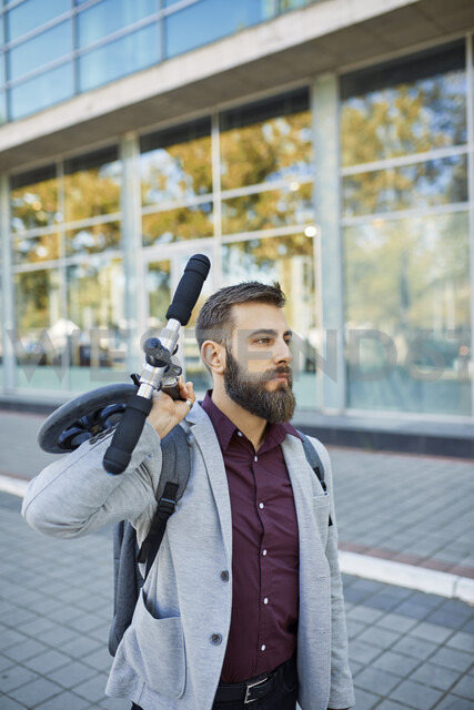 Businessman carrying scooter - ZEDF01725