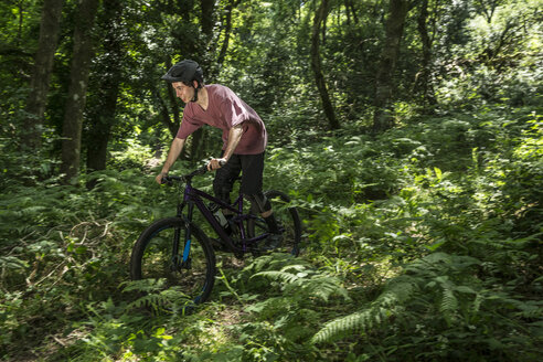 Man mountain biking in forest - LUXF01846