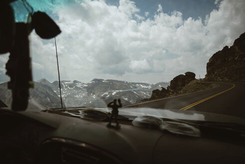 Car moving on mountain road against cloudy sky at Rocky Mountain National Park - CAVF51503