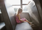 Side view of girl sitting by window in bus - CAVF51509