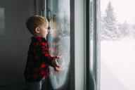 Side view of boy looking through window while standing at home during winter - CAVF51539