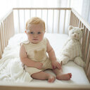 Portrait of cute baby boy sitting in crib at home - CAVF51554