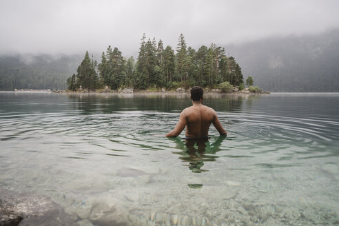 Shirtless man swimming in lake at forest - CAVF51566