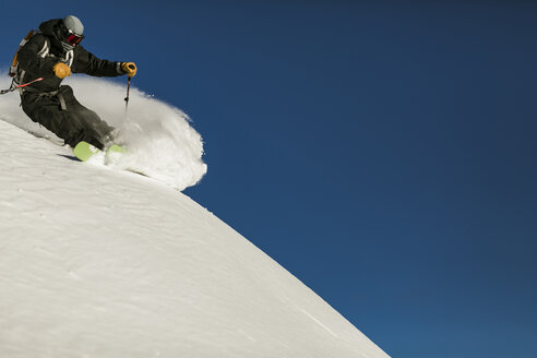 Low angle view of man skiing on snow covered mountain against clear blue sky - CAVF51578