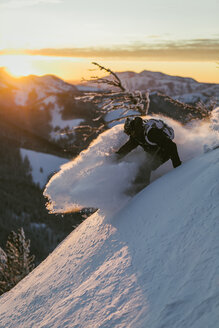 Side view of man skiing on snow covered mountain against sky during sunset - CAVF51581