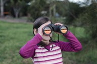 Girl looking through binoculars while standing at park - CAVF51584