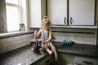 Girl preparing food in container while sitting on kitchen counter at home - CAVF51590