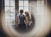 Rear view of boy with dog looking through window seen through glass at home - CAVF51626
