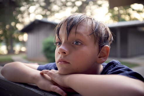 Close-up of thoughtful boy looking away while leaning on bench at park - CAVF51647