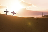 Silhouette friends with surfboards walking at desert during sunset - CAVF51656