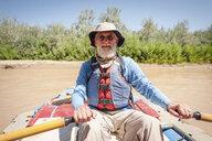 Portrait of senior man kayaking in river - CAVF51659