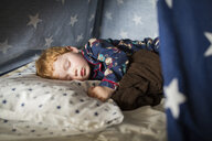 Close-up of cute boy sleeping on bed in tent at home - CAVF51662