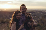Portrait of young couple with dog standing on field during sunset - CAVF51668