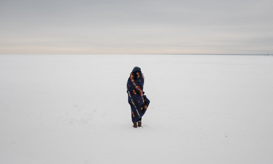 Rear view of woman wrapped in blanket standing on snow covered landscape against sky - CAVF51719