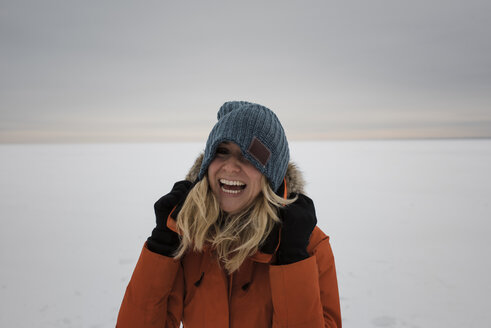 Happy woman standing on snow covered landscape against cloudy sky - CAVF51722
