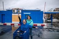 Woman pushing friend sitting in shopping cart on wet street against sky - CAVF51806