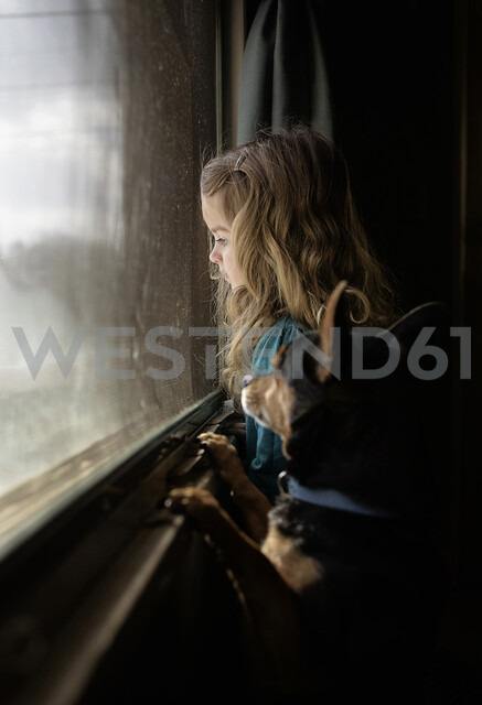 Side view of girl and dog looking through window in darkroom - CAVF51818