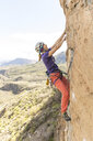 Side view of female hiker wearing helmet while climbing mountain - CAVF51827