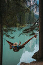 High angle view of young woman resting in hammock against lake - CAVF51842
