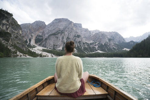Rear view of woman sitting in boat on river amidst mountain against sky - CAVF51854