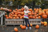 Portrait of playful girl sticking out tongue while holding pumpkin - CAVF51866