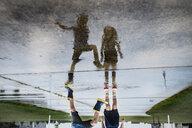 Upside down image of siblings standing on wet footpath - CAVF51869