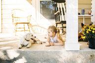 Girl lying by dog on porch - CAVF51875