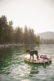 Girl with dog lying on pool raft in lake against clear sky - CAVF51902