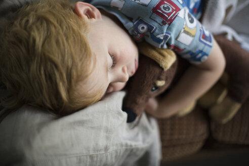 Boy with teddy bear sleeping on sofa at home - CAVF51926