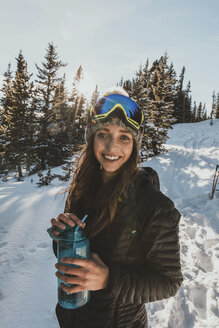 Portrait of smiling young woman wearing ski goggles while holding water bottle on snowy field - CAVF51935