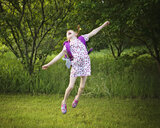 Cheerful girl with backpack jumping over grassy field at park - CAVF51962