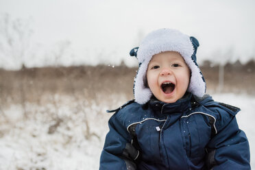 Portrait of cute playful baby boy shouting while wearing warm clothing during winter - CAVF51971