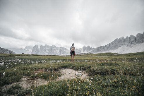 Rear view of female hiker standing on grassy field against cloudy sky - CAVF52043
