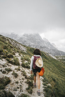 Rear view of female hiker walking on mountain against cloudy sky - CAVF52046