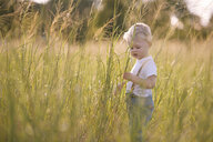 Side view of baby boy standing on grassy field - CAVF52097