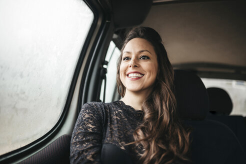 Smiling woman looking away while traveling in car - CAVF52112
