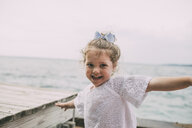 Portrait of cheerful girl against sea and clear sky - CAVF52142