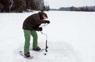Man drilling frozen lake with ice auger standing against sky - CAVF52154