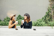 Cheerful female friends having drinks while sitting at table against wall - CAVF52214