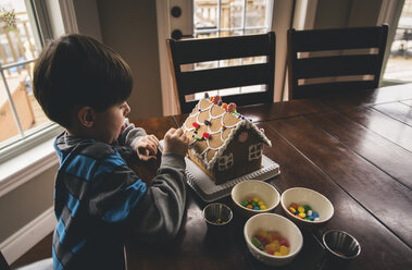 High angle view of boy making gingerbread house on wooden table during Christmas at home - CAVF52232