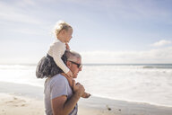 Side view of grandfather carrying granddaughter on shoulders while standing at beach against sky - CAVF52268