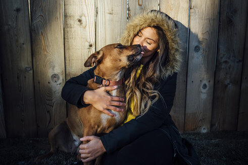 Woman with dog sitting against wooden fence - CAVF52286