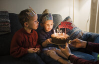 Children looking at birthday cake held by father at home - CAVF52322