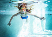 Portrait of girl swimming underwater in pool - CAVF52325